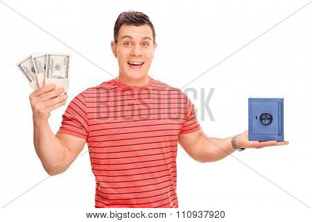 Cheerful guy holding few stacks of money and a small blue safe isolated on white background