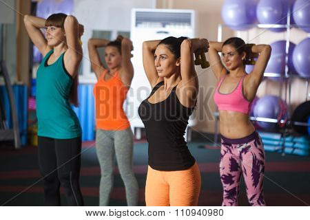 group of four women traning with dumbbells