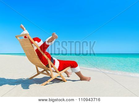 Christmas Santa Claus Enjoy Sun On Deckchair At Sandy Beach