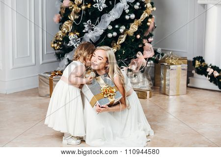 happy family mother and daughter at  New Year with gifts around the Christmas tree