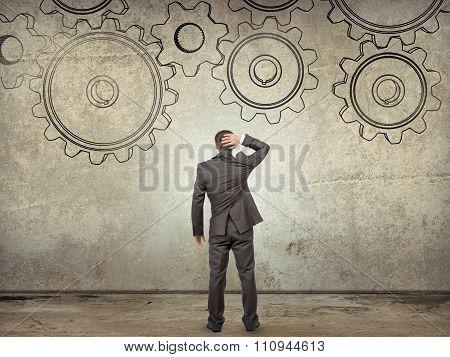 Businessman looking at cog wheels, rear view