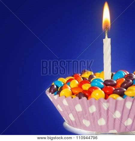 Decorated Birthday cupcake with one lit candle and colorful candies on dark blue background.