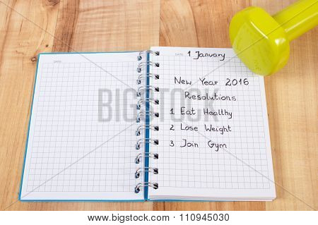 New Years Resolutions Written In Notebook And Dumbbells