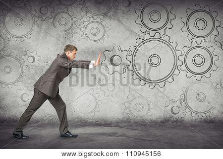 Businessman pushing cog wheels