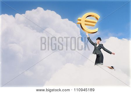 Young businesswoman in suit and bowler hat catching euro symbol
