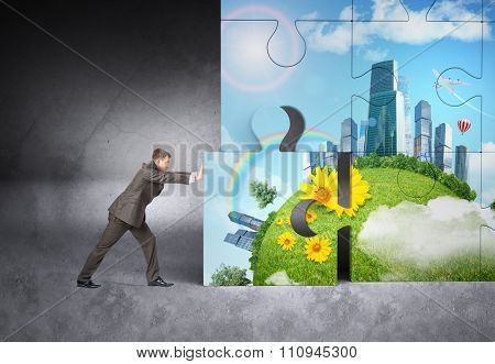 Man pushing puzzle piece of city picture