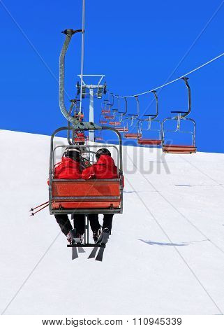 Skiers Couple On Ski Lift Against Winter Snowy Mountain Landscape