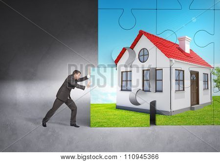 Man pushing puzzle piece of red house picture