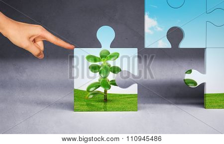 Man hand pushing puzzle piece of money tree