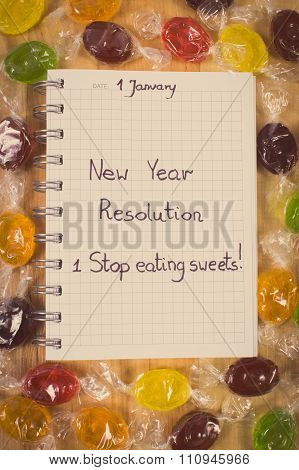 Vintage Photo, New Years Resolutions Written In Notebook And Colorful Candies