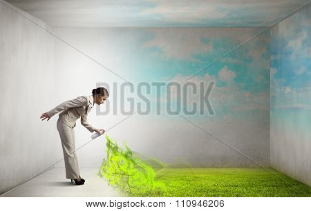 Young businesswoman spraying green grass from aerosol balloon