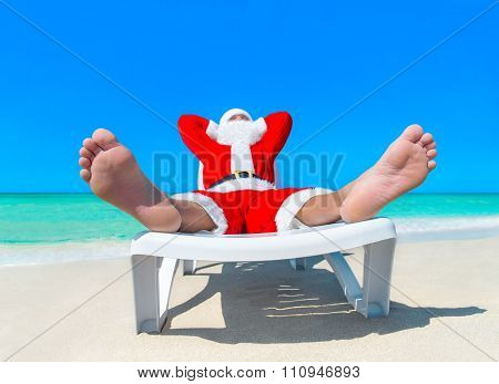 Santa Claus Resting Sunbathing On Deck Chair At Tropical Beach