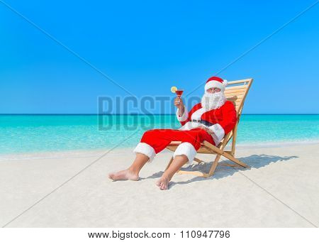 Christmas Santa Claus With Cocktail On Deck Chair At Beach