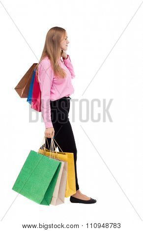 back view of going  woman  with shopping bags . beautiful girl in motion.   Isolated over white background. The girl in the pink shirt is the right throwing shopping bags on her shoulder.