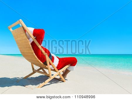 Christmas Santa Claus Relaxing On Deckchair At Ocean Tropical Beach