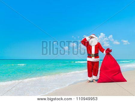 Santa Claus With Big Christmas Sack At Tropical Sandy Beach