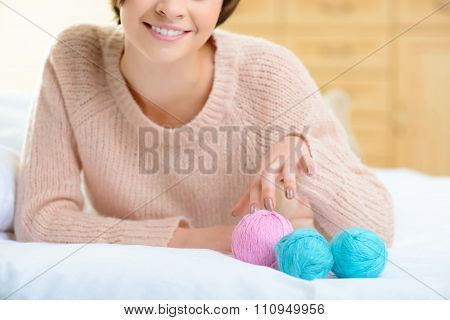 Young girl with wool yarn for knitting.