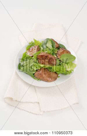 plate of pan fried liver with greens on white place mat