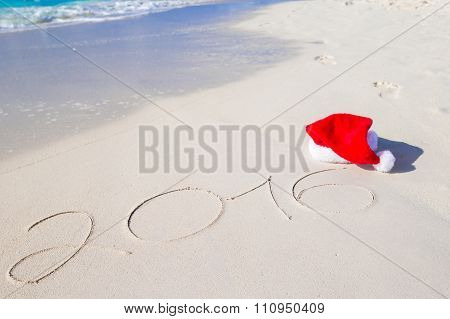2016 and Merry Christmas written on beach white sand with red Santa hat