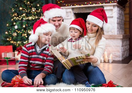 Family reviewing their photos in album near Christmas tree in front of fireplace