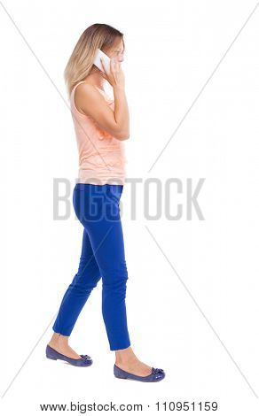 side view of a woman walking with a mobile phone. back view ofgirl in motion.  backside view of person.  Isolated over white background. Blonde in blue pants right away speaking on white smartphone