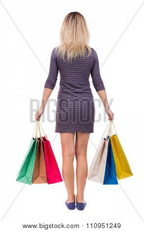 back view of woman with shopping bags . beautiful brunette girl in motion.  backside view of person.  Isolated over white background. Girl in a short dress is holding in both hands paper bags.
