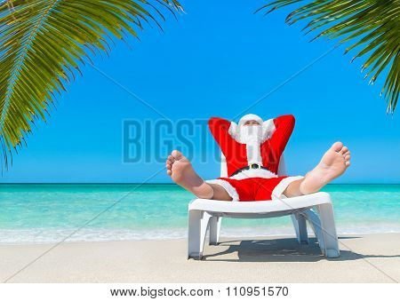 Christmas Santa Claus Sunbathing On Sun Bed At Palm Beach