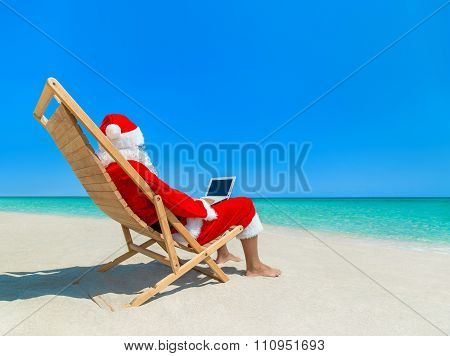 Christmas Santa Claus At Beach In Deckchair Work Using Laptop