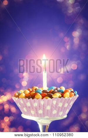 Decorated Birthday cupcake with one lit candle and colorful candies on blue background.