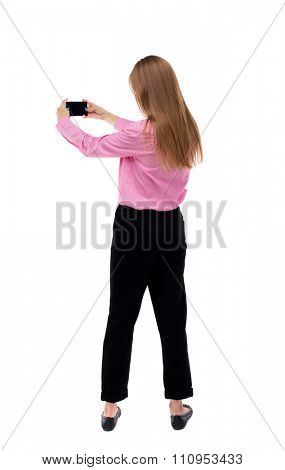 back view of standing young beautiful  woman  and using a mobile phone. girl  watching.  backside view of person.  Isolated over white background. Turning left the girl removes a smartphone video.