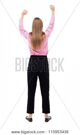 Back view of  business woman.  Raised his fist up in victory sign. Raised his fist up in victory sign.  Isolated over white background. girl office worker in black trousers dancing raised their hands.