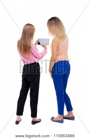 Back view of two young woman look at the smart phone. Rear view people collection.  backside view of person. Rear view. Isolated over white . Two blonde girls looking at something in tablet PC.
