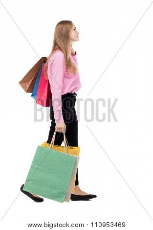 back view of going  woman  with shopping bags . beautiful girl in motion.  backside view of person.  Isolated over white . girl in a pink shirt with bags goes to the right and looks in front of him.