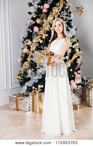 christmas, x-mas, winter, happiness concept - smiling woman with gift