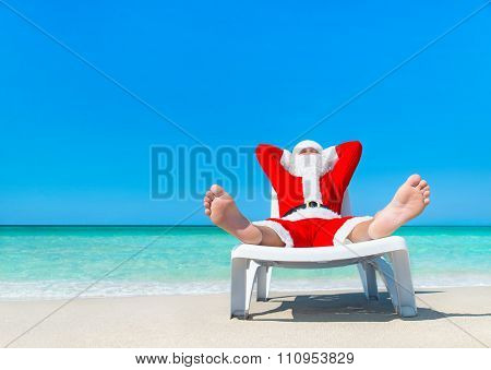 Christmas Santa Claus Sunbathing On Sun Bed At Tropical Beach