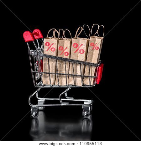 Concept Of Black Friday Shopping Cart With Paper Bags Percent Is Isolated On Black Background