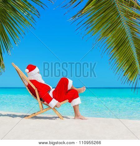Christmas Santa Claus Resting On Deckchair At Tropical Palm Beach