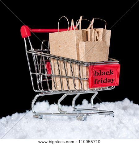 Concept Of Black Friday Shopping Trolley With Paper Bags In Snow Is Isolated On Black Background
