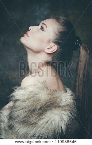 beautiful young woman with artificial fur  portrait, studio shot, profile