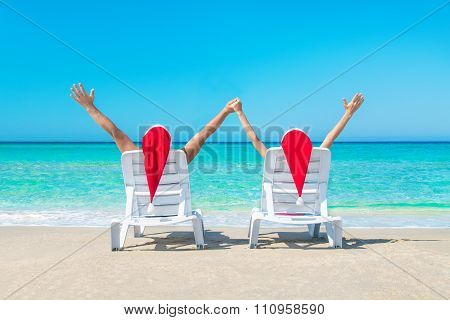 Young Couple Hands Up In Sunloungers At Ocean Beach