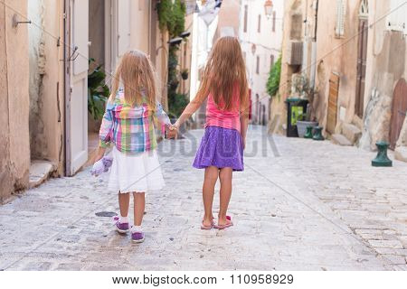 Adorable happy little girls walking outdoors in European city