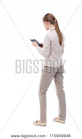 back view of standing young beautiful  girl with tablet computer in the hands of. girl  watching.  Isolated over white background. A girl in a white jacket turned to the left to read electronic books.