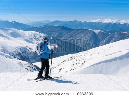 Skier In Alpine Skis Go Skiing In Snowy Mountains Landscape