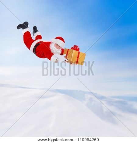 Santa Claus Flying With Christmas Gift Above Snowy Landscape