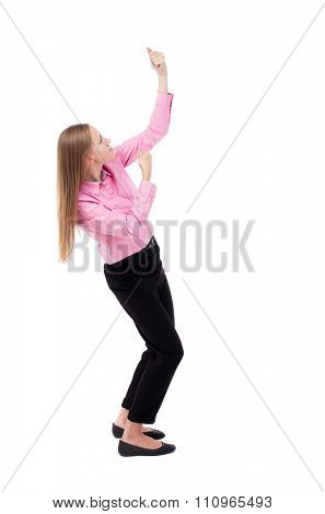 back view of standing business woman pulling a rope from the top or cling to something. Isolated over white background. girl office worker in black slacks standing sideways pulls a rope from top down
