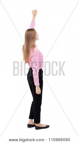 Back view business woman. Raised his fist up in victory sign. Raised his fist up in victory sign. Isolated over white. girl office worker in black slacks standing sideways holding up hand up