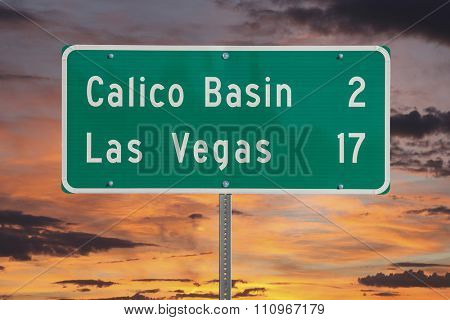 Las Vegas highway sign with sunset sky.