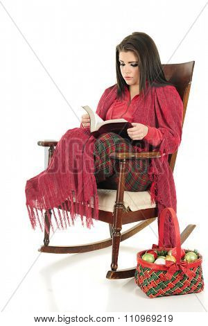 A beautiful teen girl cozied up in her PJs and a blanket as she reads her Bible in a rocking chair.  A basket of Christmas bulbs on the floor nearby.  On a white background.