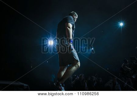 MMA fighter in dark comes to ring. background fans
