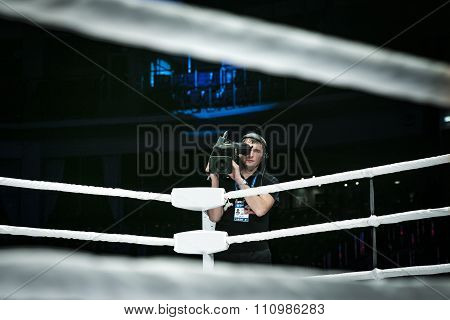 male videographer with a camera broadcast live from corner of ring